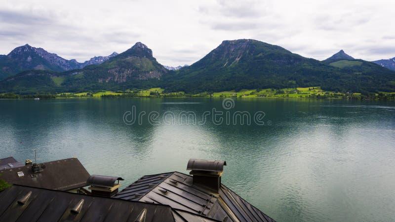 Красивый ландшафт Aps с большим озером, зелеными горами, лесом и крышами hauses стоковое фото