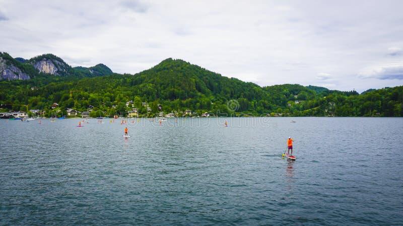 Красивый ландшафт Aps с большим озером окруженным зелеными горами, плавая люди стоковые изображения rf