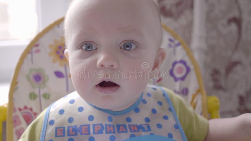 Красивый маленький мальчик малыша сидя на таблице детей в голубом bib, наблюдая в камеру и лепеча близко вверх стоковое изображение rf
