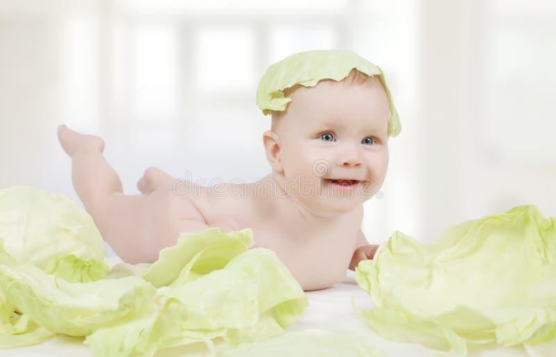 Красивый маленький младенец с зеленой капустой стоковое изображение rf