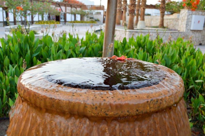 Красивый маленький фонтан в форме коричневой вазы, кувшина с понижаясь падениями воды на покрашенный стоять камней стоковые изображения