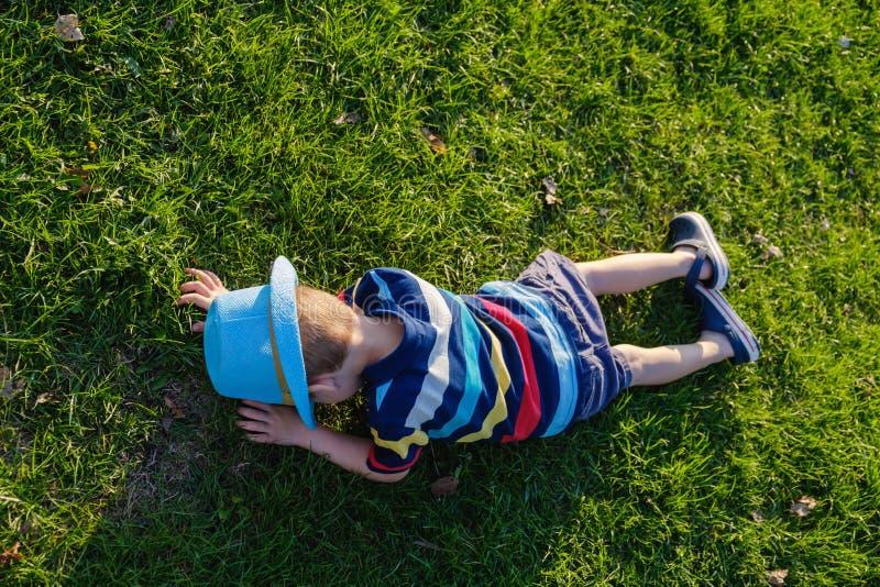 Красивый мальчик лежа на траве Немногое фантазер лежит в луге со шляпой Ребенок в природе вне города Беспечальные каникулы стоковые фото