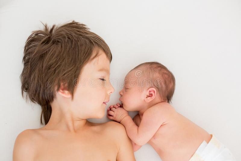 Красивый мальчик, обнимающ с нежностью и заботит его newborn младенец стоковое изображение