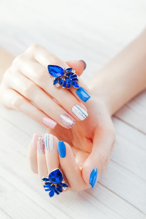 Красивый маникюр с серьгами Сочетание из голубое, белые, розовые цвета Женские руки с стильным маникюром стоковое изображение
