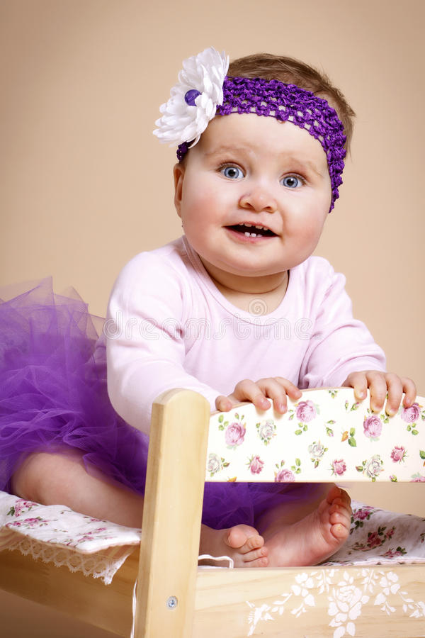 Красивый маленький младенец сидя на кровати стоковые фото