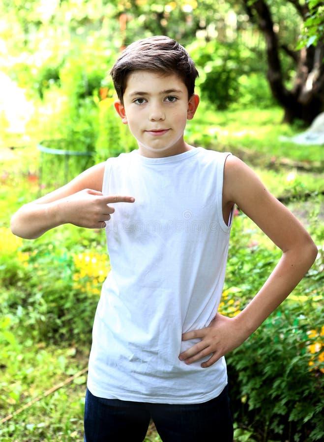 красивый мальчик в белой футболке освобождает надписи стоковое фото