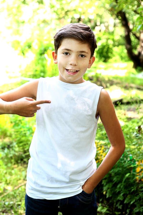 красивый мальчик в белой футболке освобождает надписи стоковые фото