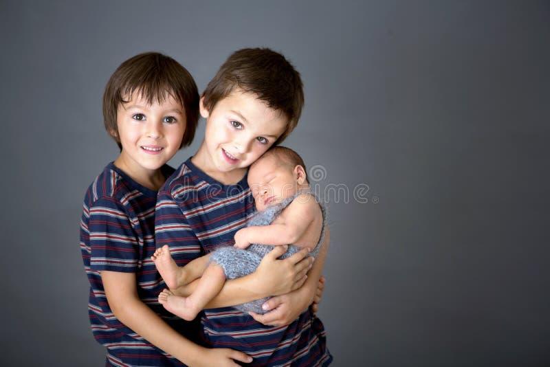Красивый мальчик, обнимающ с нежностью и заботит его newborn младенец стоковые изображения