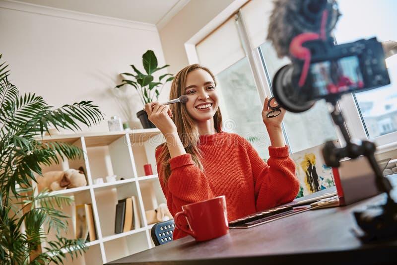 Красивый! Милый и молодой блоггер используя щетку для приложения продукта красоты пока записывающ новую видео- консультацию стоковые изображения rf