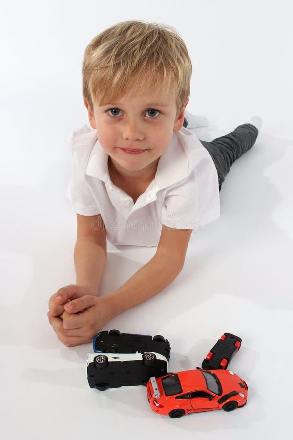 Красивый милый мальчик лежа за пуком игрушек автомобиля и усмехаясь задушевно стоковые изображения rf
