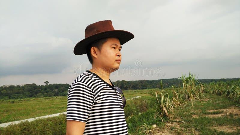 Красивый милый азиатский человек при шляпа Cowbow смотря заход солнца стоковое изображение rf