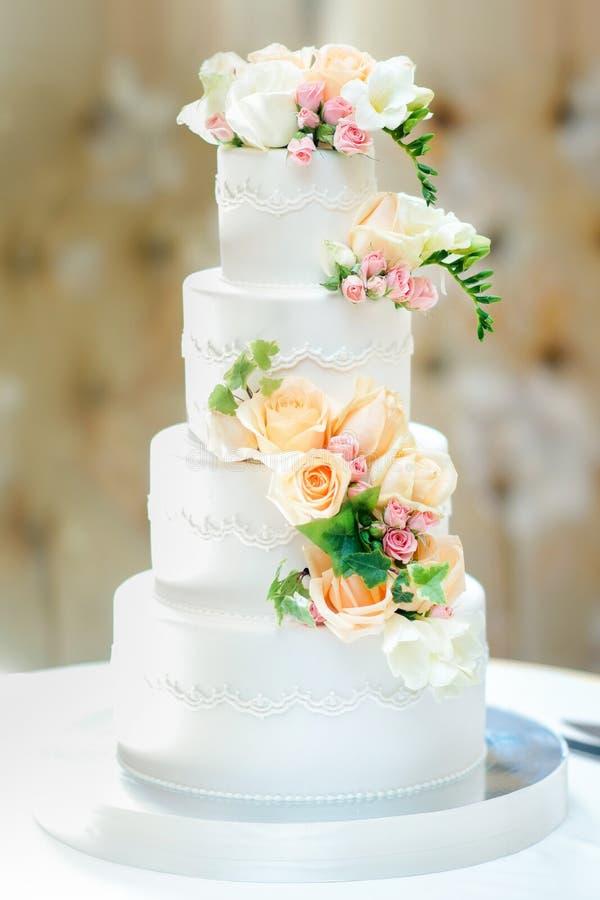 Красивый многоуровневый украшенный свадебный пирог с свежими цветками стоковая фотография rf