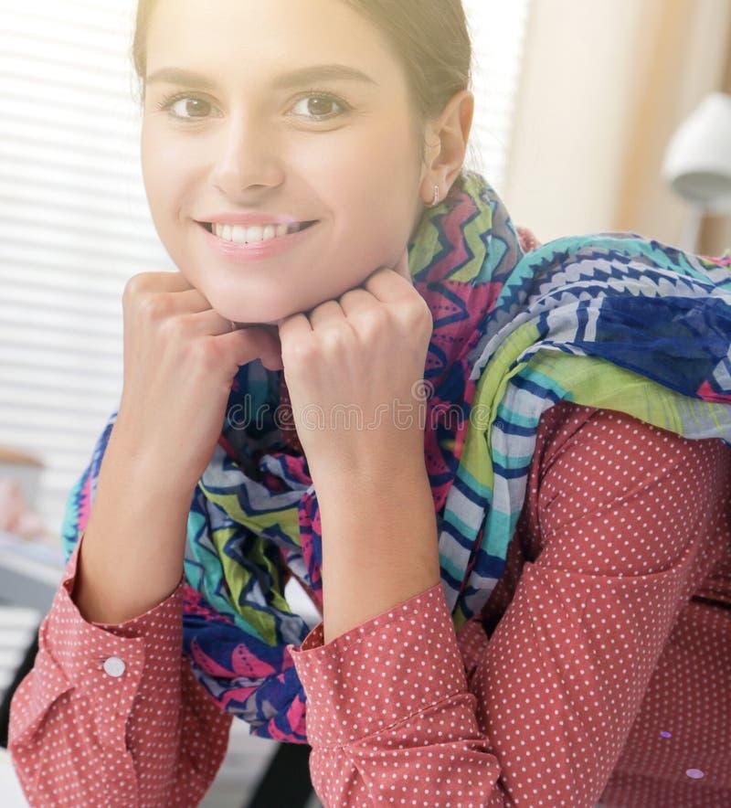 Красивый модельер сидя на столе в студии стоковое изображение