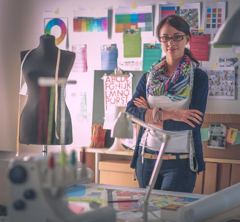 Красивый модельер стоя в студии стоковое изображение