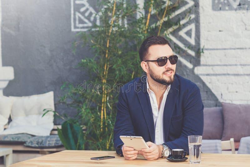 Красивый модный парень сидя в кофейне и держа цифровой прибор планшета стоковая фотография