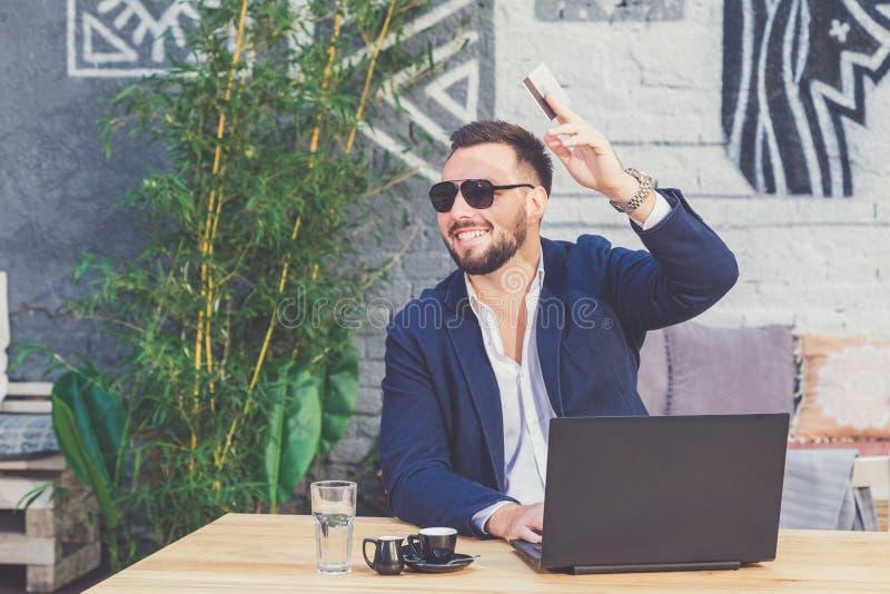 Красивый модный человек спрашивая оплатить с его кредитной карточкой в кофейне стоковые фото