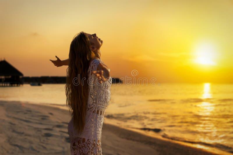 Красивый, молодая женщина в белом платье обнимая золотой заход солнца стоковая фотография