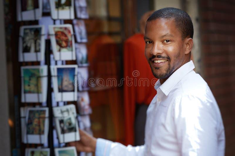 Красивый молодой африканский человек в белой рубашке смотря камеру и выбирает открытку стоковое изображение rf