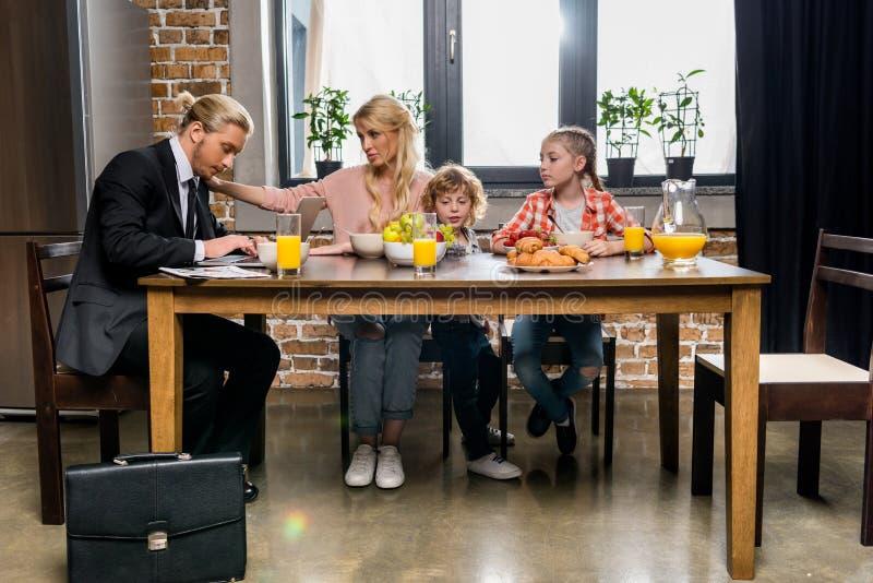 красивый молодой бизнесмен имея завтрак с семьей стоковая фотография