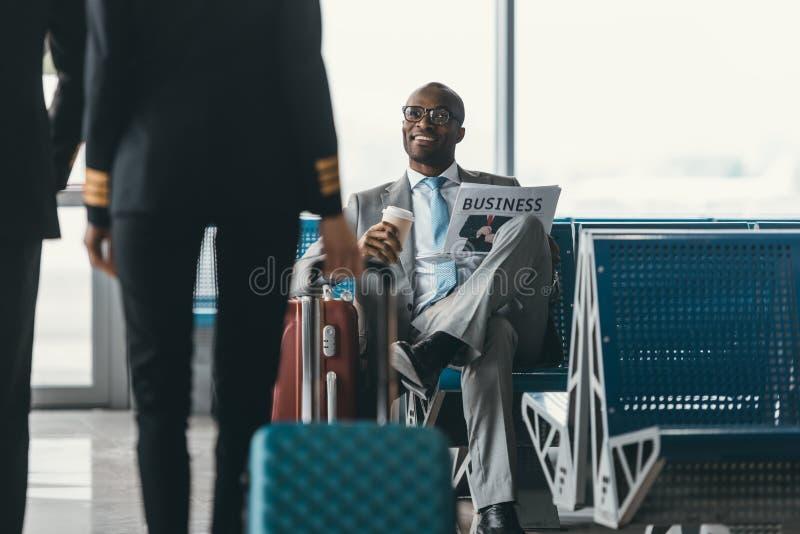 красивый молодой бизнесмен смотря женского пилота проходя мимо пока ожидание для полета стоковые фото
