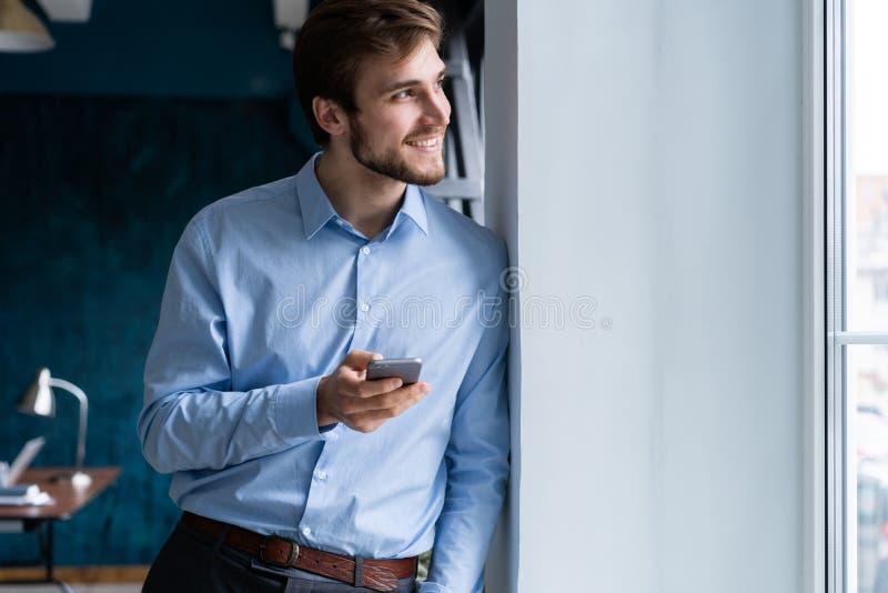 Красивый молодой бородатый бизнесмен в офисе используя мобильный телефон внутри помещения стоковое фото rf