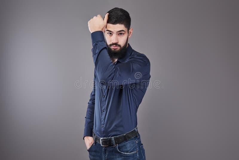 Красивый молодой бородатый человек смотрит отсутствующим пока стоящ против серой предпосылки стоковые фото