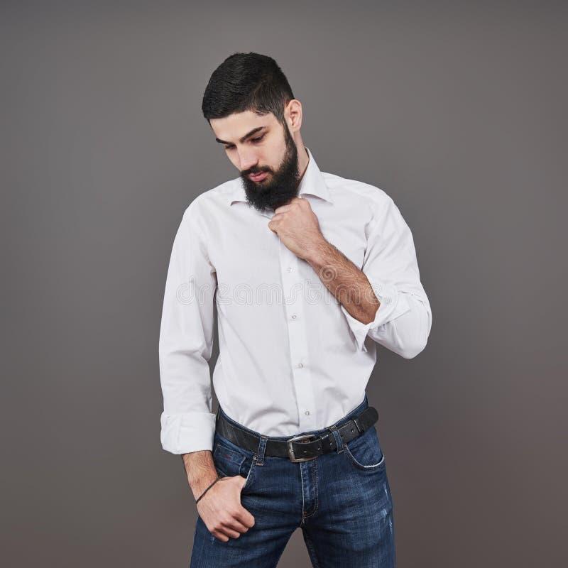 Красивый молодой бородатый человек смотрит отсутствующим пока стоящ против серой предпосылки стоковое фото