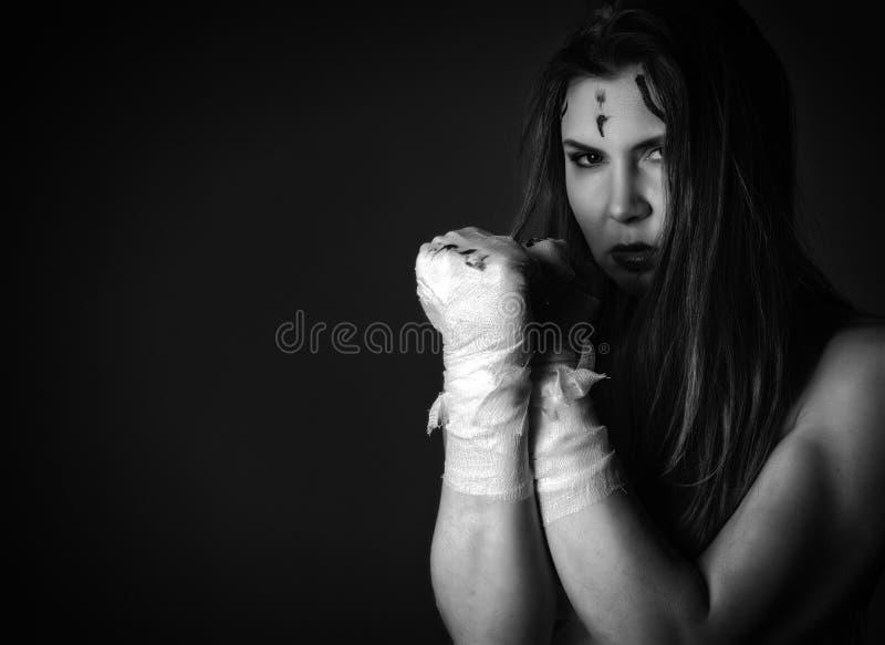Красивый молодой женский боец после боя на темной предпосылке девушки в боевых искусствах черная белизна открытый космос стоковое изображение