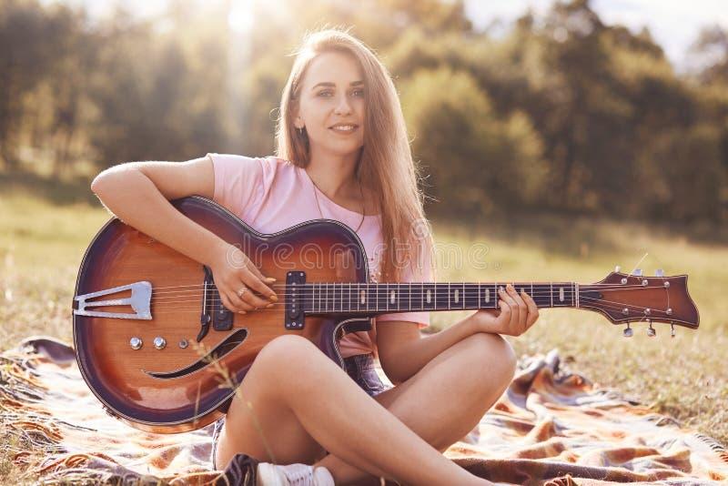 Красивый молодой женский музыкант сидит пересеченные ноги, смотрит с положительным выражением на камере, гитаре игр акустической, стоковые фото
