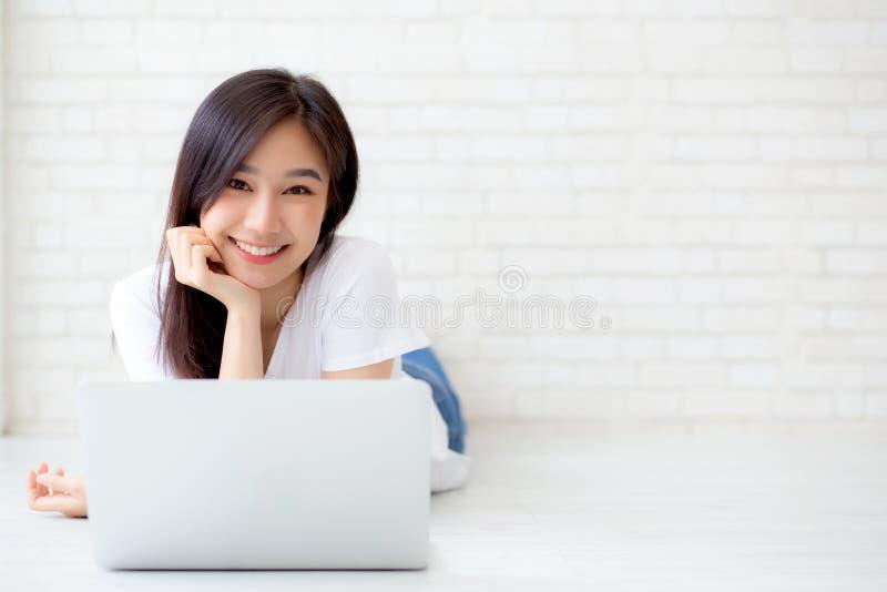 Красивый молодой женщины портрета азиатской работая онлайн компьтер-книжка лежа на предпосылке цемента кирпича пола стоковые фотографии rf