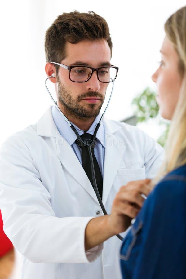 Красивый молодой мужской доктор проверяя биение сердца красивой молодой женщины терпеливое используя стетоскоп в медицинском офис стоковое фото