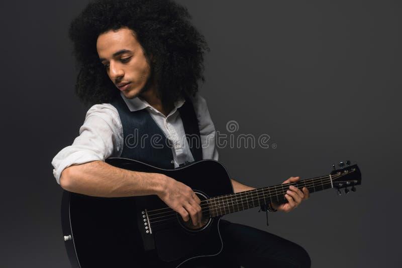 красивый молодой музыкант играя акустическую гитару стоковая фотография rf
