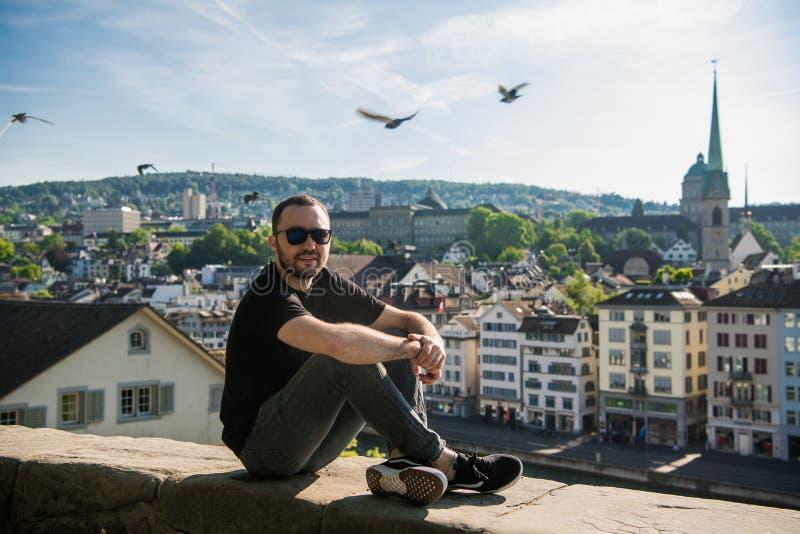 Красивый молодой парень сидеть в парке города с видом на город в Цюрих, Швейцарии стоковая фотография rf