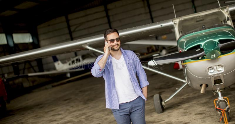 Красивый молодой пилот проверяя самолет в ангаре и используя m стоковое фото