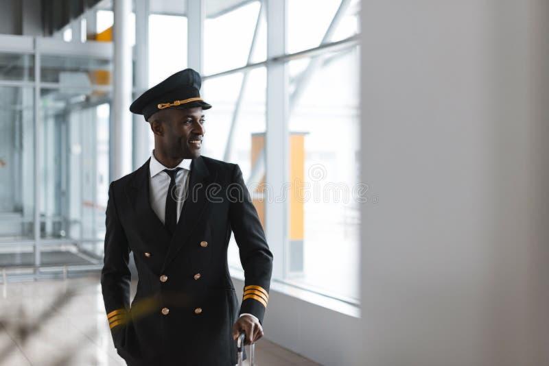 красивый молодой пилот с багажом на авиапорте стоковые фото