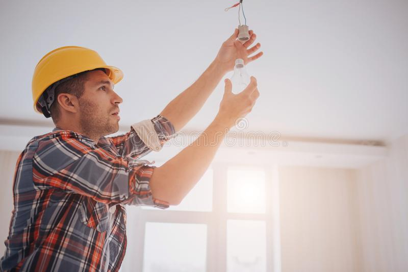 Красивый молодой построитель в желтом шлеме конструкции переплетает электрическую лампочку внутри Человек смотрит вверх стоковые изображения rf