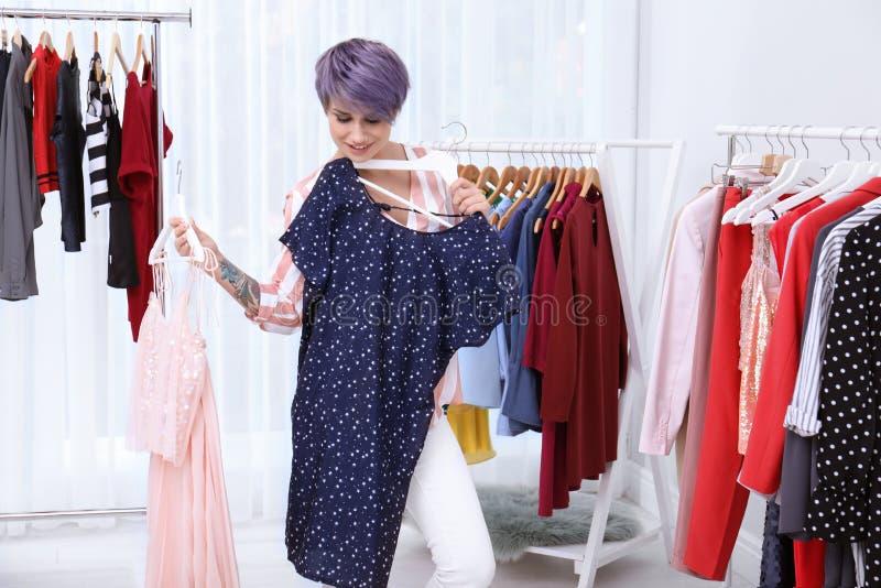 Красивый молодой стилизатор выбирая одежды стоковые изображения rf
