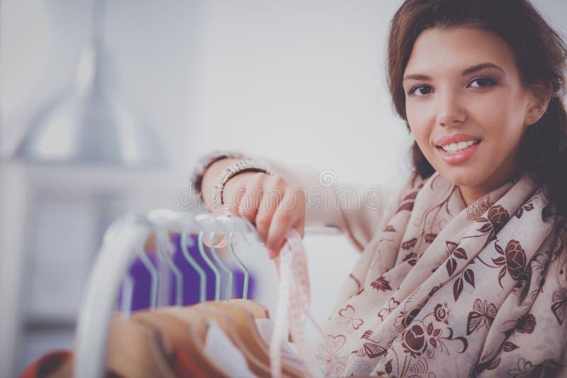 Красивый молодой стилизатор около шкафа с вешалками в офисе стоковое фото rf