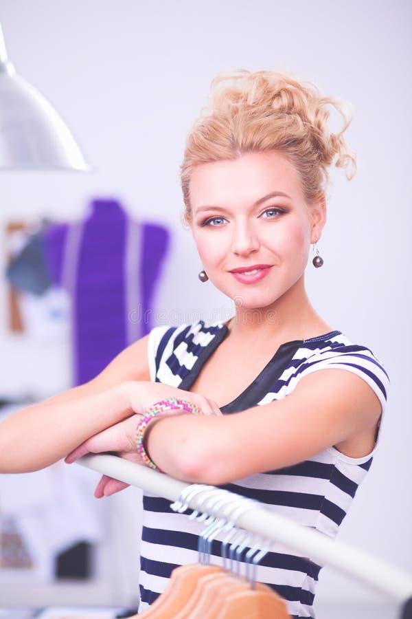 Красивый молодой стилизатор около шкафа с вешалками в офисе стоковые изображения