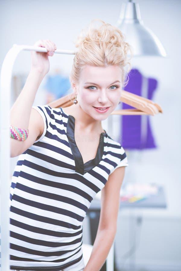 Красивый молодой стилизатор около шкафа с вешалками в офисе стоковые изображения rf