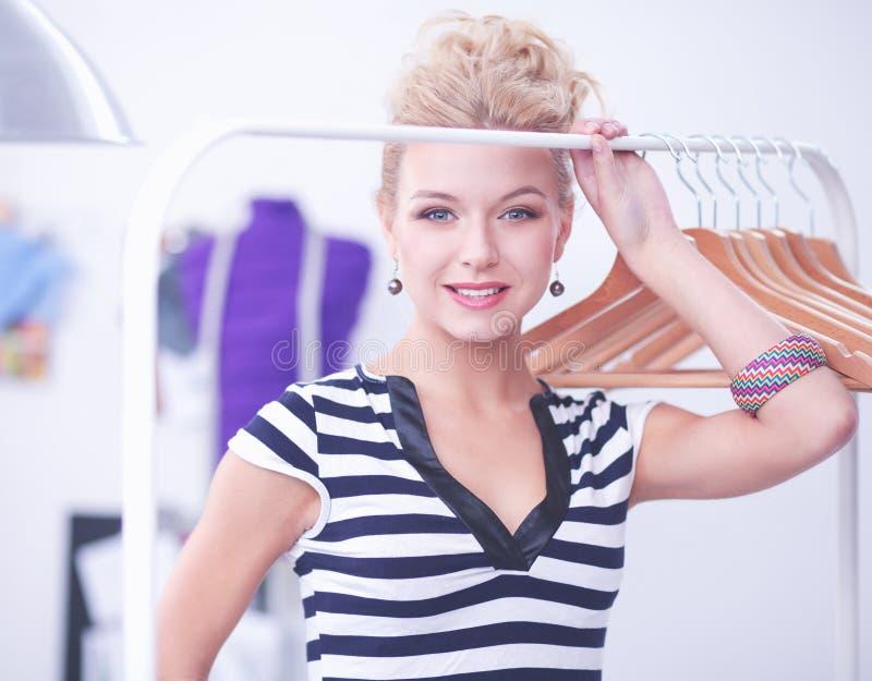 Красивый молодой стилизатор около шкафа с вешалками в офисе стоковые фотографии rf