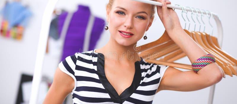 Красивый молодой стилизатор около шкафа с вешалками стоковые изображения rf