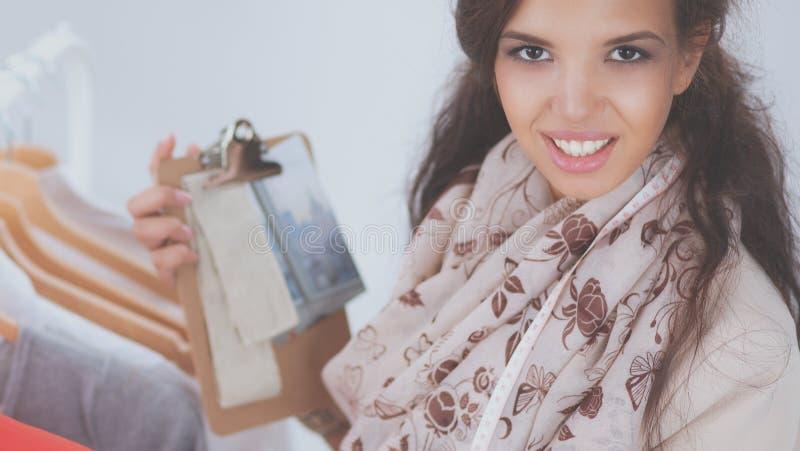 Красивый молодой стилизатор около шкафа с вешалками стоковое изображение