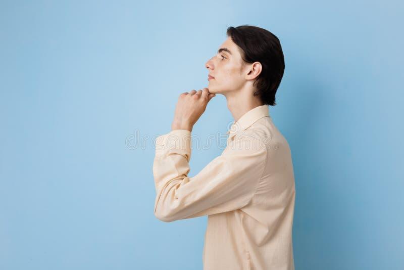 Красивый молодой тонкий темн-с волосами парень с голубыми глазами нося желтую руку удерживания рубашки на подбородке представляя  стоковые изображения