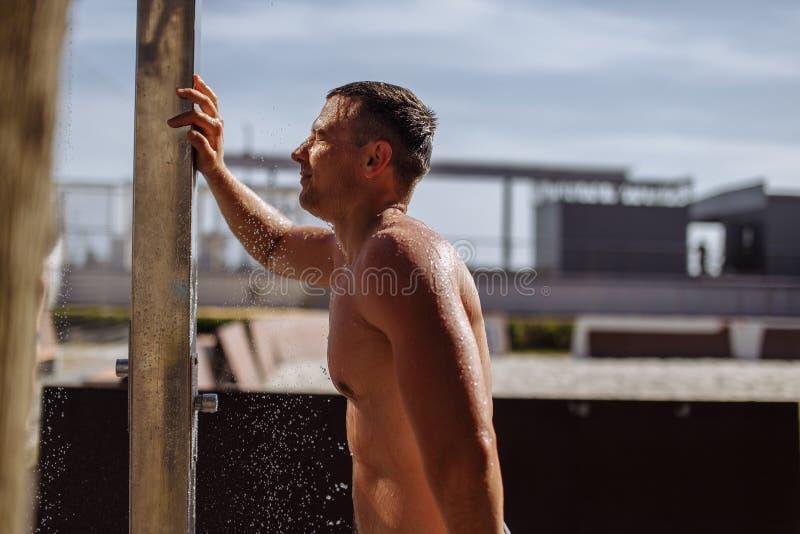 Красивый молодой топлесс кавказский человек принимая душ на открытом воздухе на пляже стоковое фото