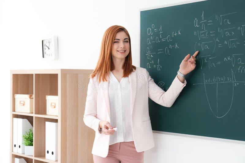 Красивый молодой учитель объясняя написанные формулы математики стоковые изображения rf