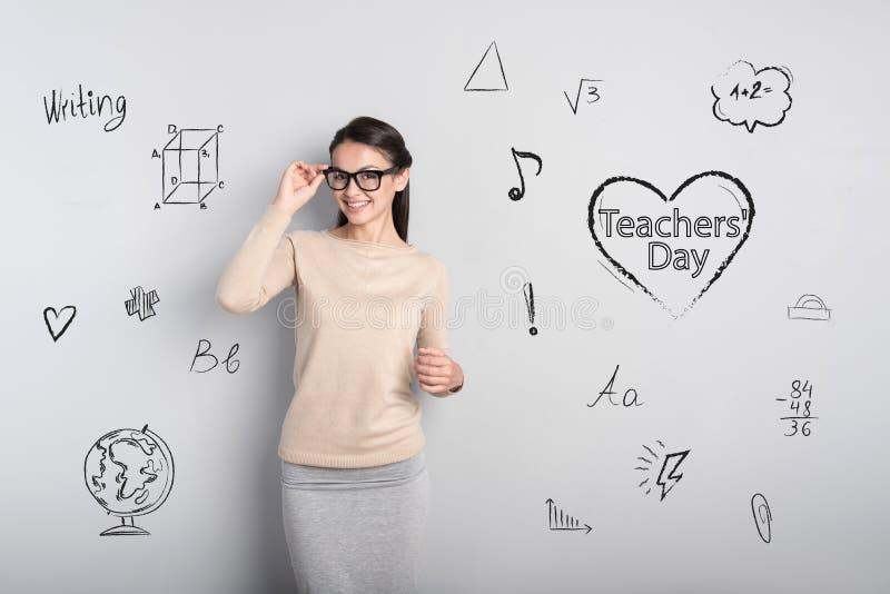 Красивый молодой учитель усмехаясь пока празднующ день учителей стоковое фото rf