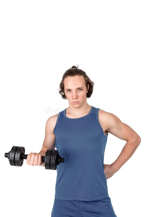 Красивый молодой человек в гантели голубой рубашки поднимаясь Белая изолированная предпосылка стоковое фото
