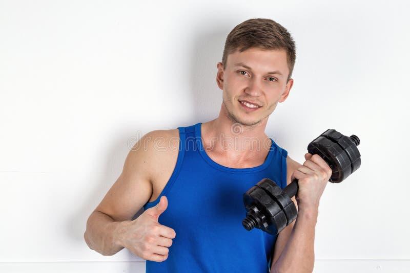Красивый молодой человек в гантели голубой рубашки поднимаясь o стоковые фотографии rf