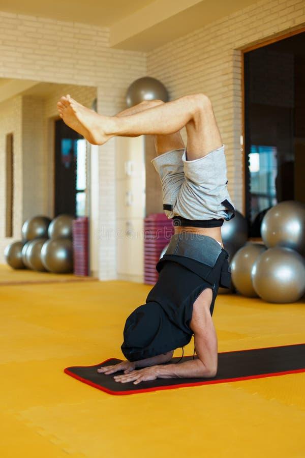 Красивый молодой человек в клобуке разрабатывая, йога, pilates стоковая фотография